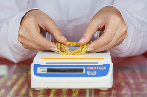 A person weighing a gold necklace on a scale - cash for gold jewelry store
