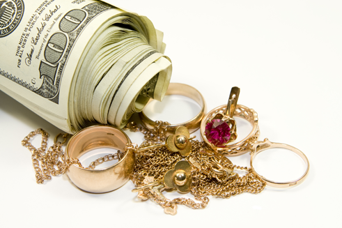 Gold rings and money next to a wad of rolled cash - cash for gold jewelry store