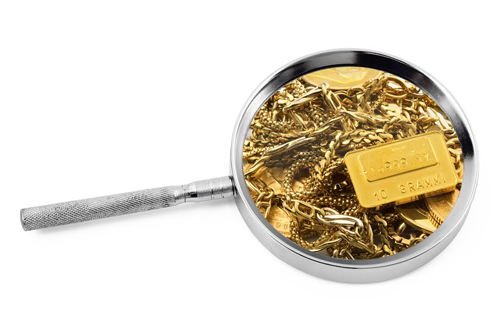 Magnifying glass examining gold jewelry - how pawn loans work